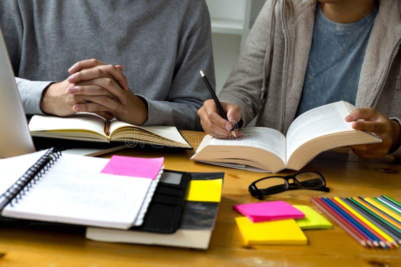 Студенты помогают преподавательству друга и вопрос учить дополнительный в библиотеке o стоковая фотография