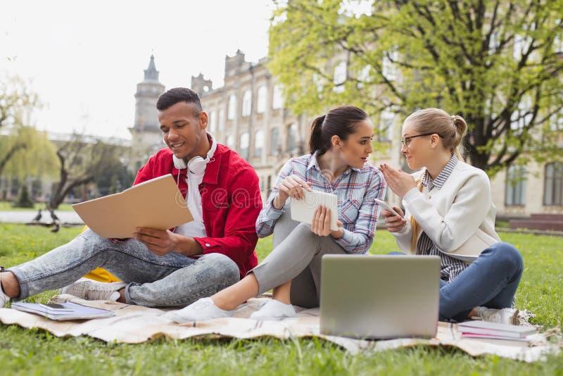 Студенты по обмену беседуя друг с другом тратящ свободное время совместно стоковые изображения rf