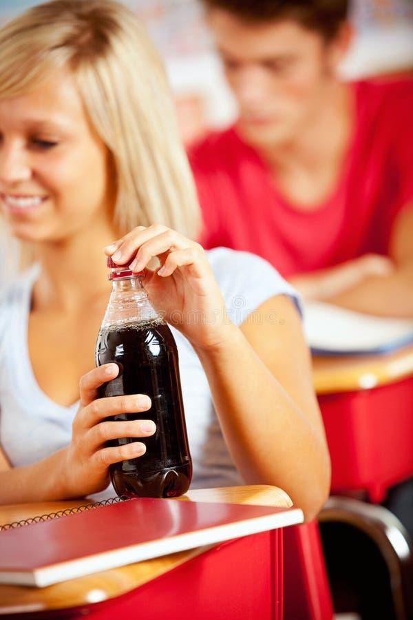 Студенты: Фокус на бутылке содовой на столе школы стоковые фотографии rf