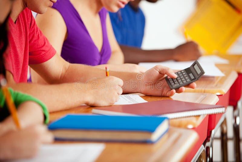 Студенты: Фокус на предназначенном для подростков используя калькулятор для того чтобы сделать домашнюю работу стоковая фотография