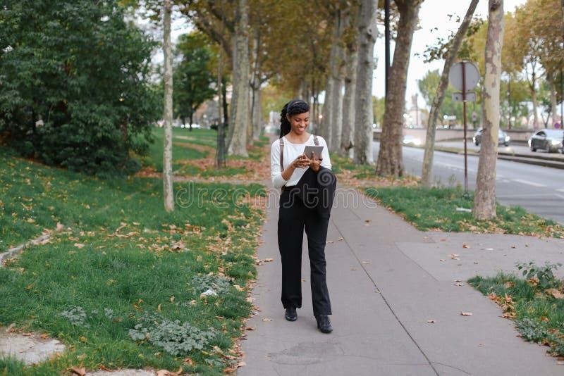 Студент Афро американский женский милый идя с таблеткой в парке осени, нося рюкзаке стоковая фотография rf