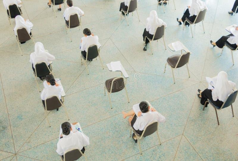 студент взгляд сверху сидит стул в университете класса для комнаты испытания образования и концепции грамотности стоковое изображение