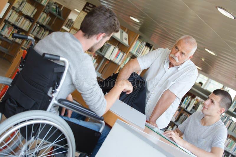 Студент в кресло-коляске в библиотеке стоковые фото