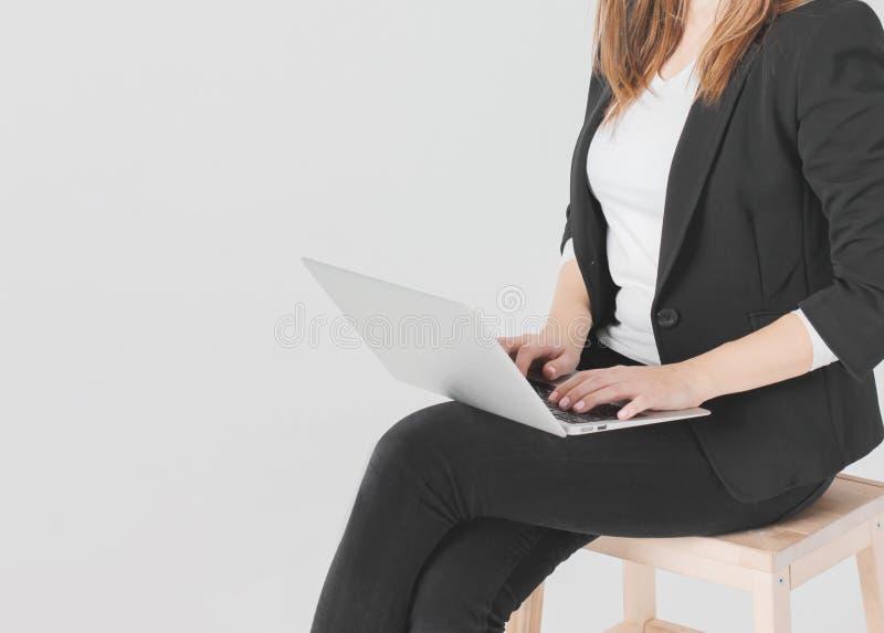 Студент дамы дела женщины в черном костюме работая на ноутбуке на серой изолированной предпосылке стоковые изображения