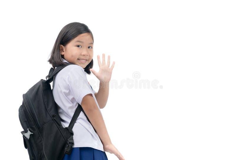Студент девушки идя к школе и развевая до свидания стоковое фото