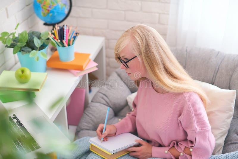 Студент делает уроки перезаписывая информацию от ноутбука в тетради домашнее обучение, работа и исследование, новые знания счастл стоковая фотография