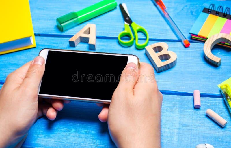 Студент держит мобильный телефон на заднем плане творческого беспорядка на настольном компьютере рабочее место студента стоковая фотография rf