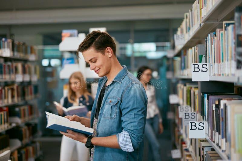Студент книги чтения университета в библиотеке стоковые изображения