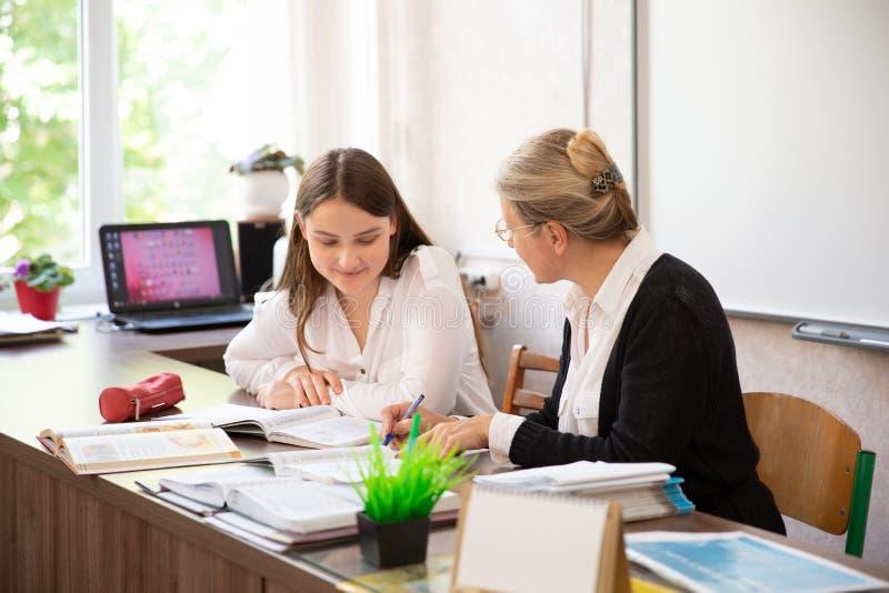 Студент колледжа имеет индивидуальное обучение от учителя в библиотеке стоковое изображение rf