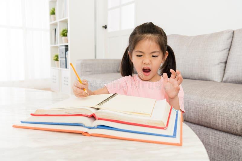 Студент маленького ребенка имеющ много домашнюю работу школы стоковое фото rf