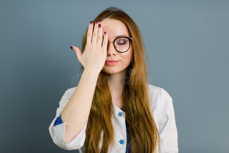 Студент-медик Медсестра Концепция дантиста медицинская Портрет доктора молодой женщины в белом пальто с закрытыми глазами и рукой стоковая фотография rf