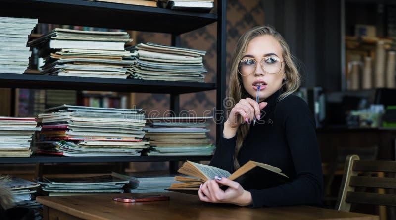 Студент молодой женщины в eyeglasses, пробуренных для того чтобы прочитать книгу в библиотеке стоковое фото