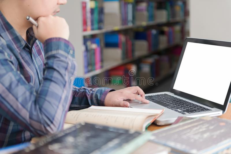 Студент подготавливая экзамен и уча уроки в школьной библиотеке, стоковое изображение rf