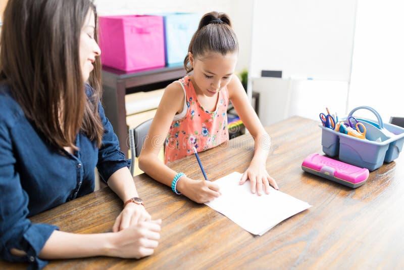 Студент порции учителя в Schoolwork дома стоковое изображение