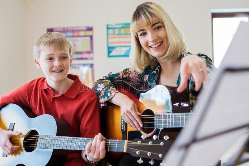 Студент порции учителя для того чтобы сыграть гитару в уроке музыки стоковые изображения