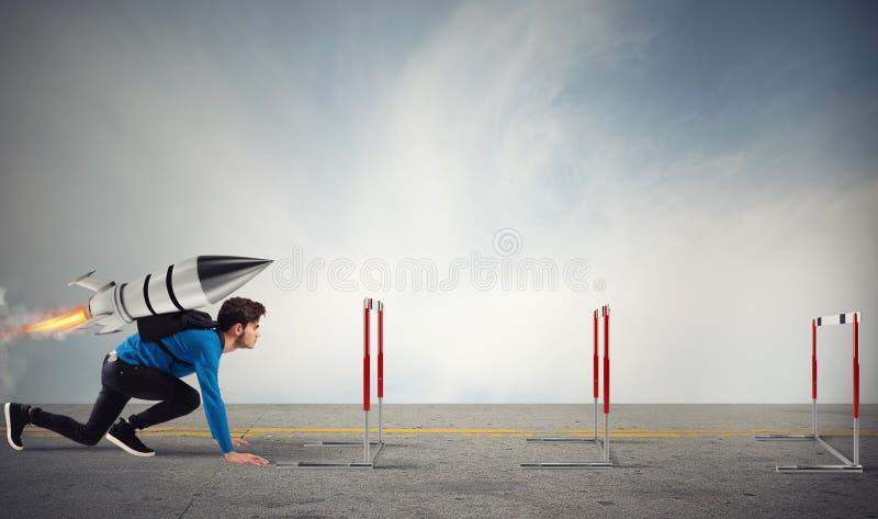 Студент преодолевает препятствия его исследований на максимальной скорости с ракетой стоковые фото