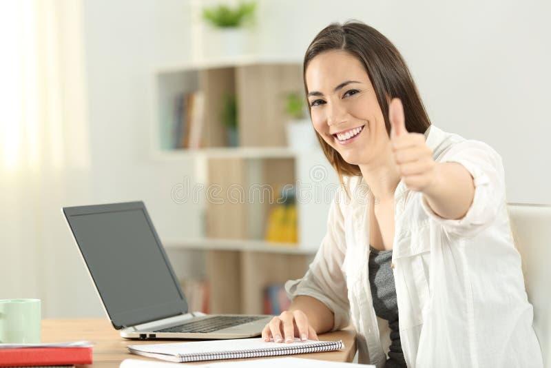 Студент университета показывать большие пальцы руки вверх дома стоковое изображение