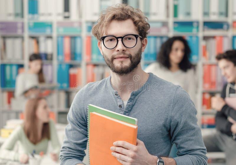 Студент университета хипстера держа тетради стоковое изображение