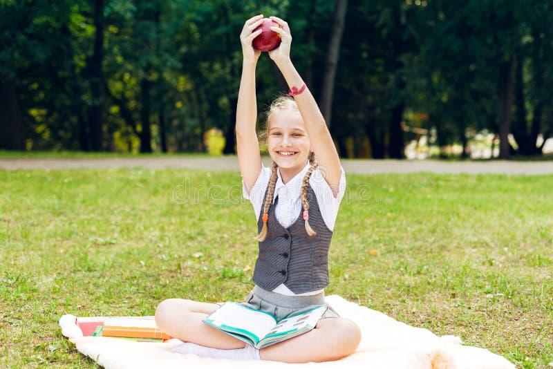 Студент усмехается счастливо и держится красное яблоко наверху школьница сидя на одеяле в парке с книгами стоковое изображение