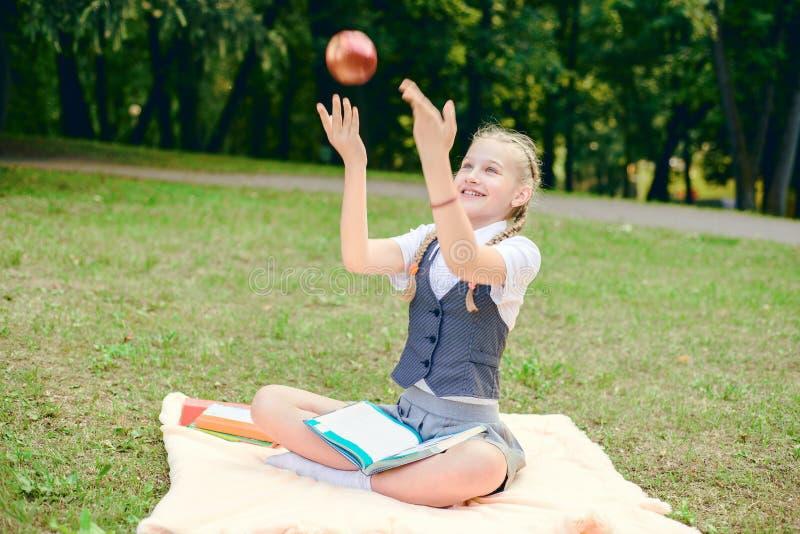 Студент усмехается счастливо и держится красное яблоко наверху школьница сидя на одеяле в парке с книгами стоковое фото rf