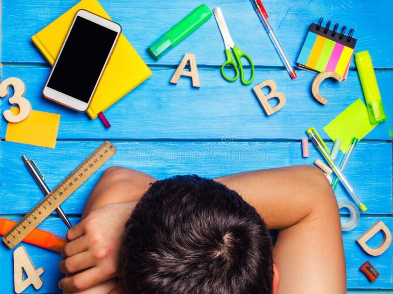 Студент уснувший в рабочем месте, творческом беспорядке Студент ленив и не хочет выучить Парень утомлен и уснувший стоковая фотография