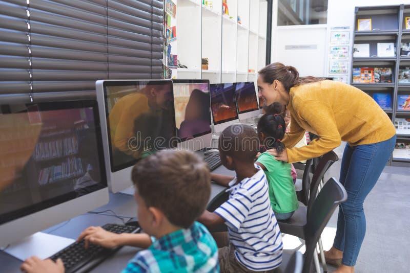 Студент учителя уча в компьютерной комнате стоковое фото