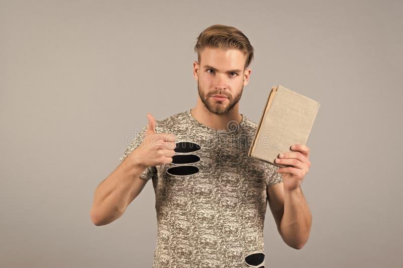 Студент человека с выставкой книги thumbs вверх по жесту рукой стоковое изображение rf