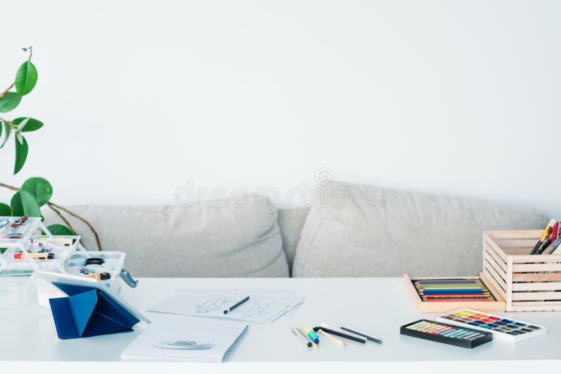 Студия необходимых инструментов рабочего места художника домашняя стоковые изображения