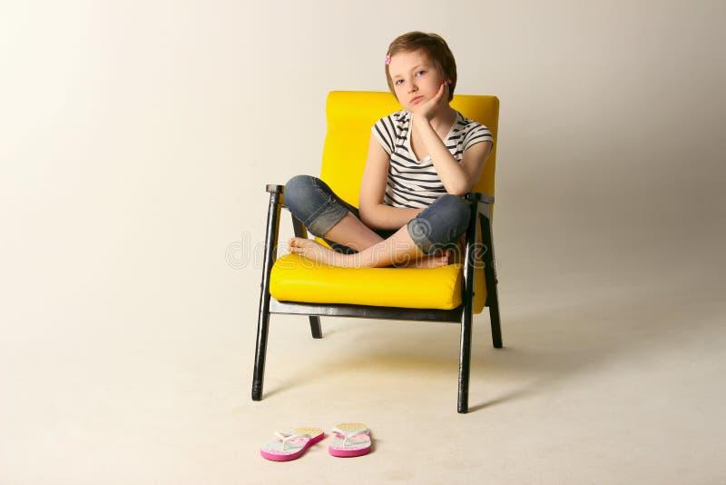 Студия сняла маленькой девочки сидя на желтом стуле стоковое фото rf