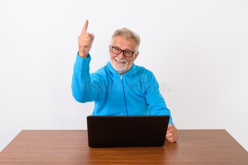Студия сняла счастливого старшего бородатого человека усмехаясь пока указывающ f стоковые изображения