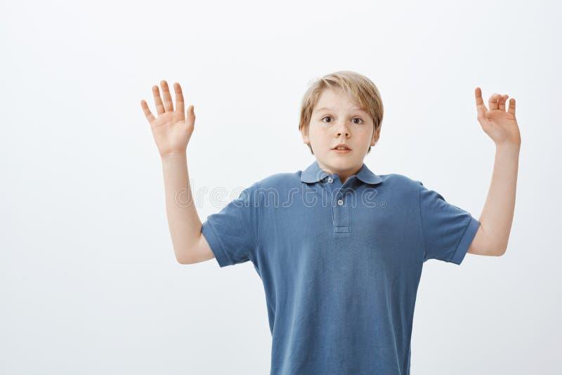Студия сняла stunned испуганного милого мальчика с белокурой головой, поднимающ ладони в сдаче, держащ дыхание и вытаращиться всп стоковая фотография