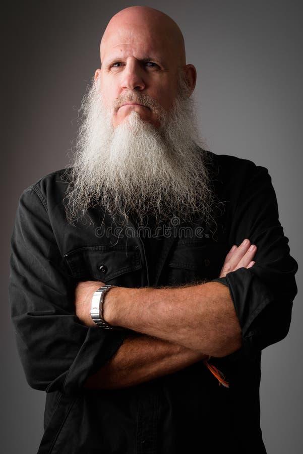 Студия снятая зрелого лысого бородатого человека выглядя серьезный с пересеченными оружиями стоковые изображения rf