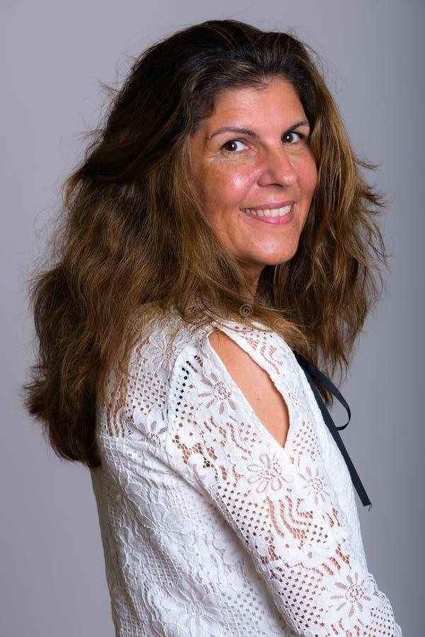 Студия снятая зрелой счастливой женщины усмехаясь пока смотрящ назад стоковые изображения rf