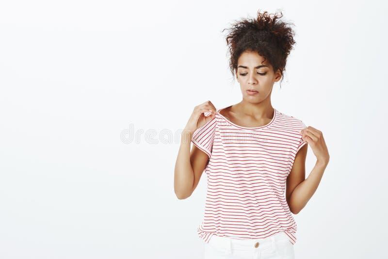 Студия снятая интенсивной смешной темнокожей женщины, касающся striped плечу футболки и вытаращить с подозрительный невзлюбить стоковые изображения rf
