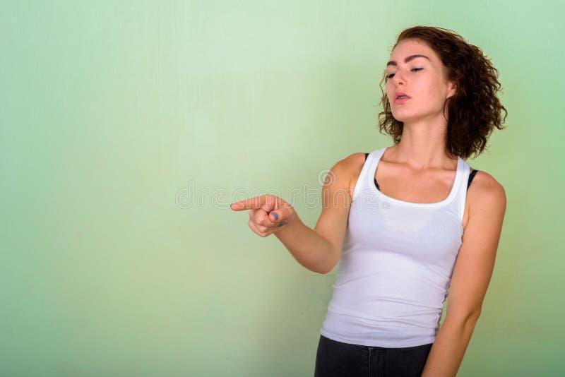 Студия снятая красивого девочка-подростка указывая на сторону снова стоковые изображения