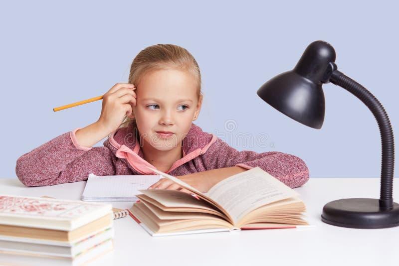 Студия снятая маленькой школьницы держит руку около головы, смотрит с внимательным выражением сразу на камере, думает о домашней  стоковое изображение rf