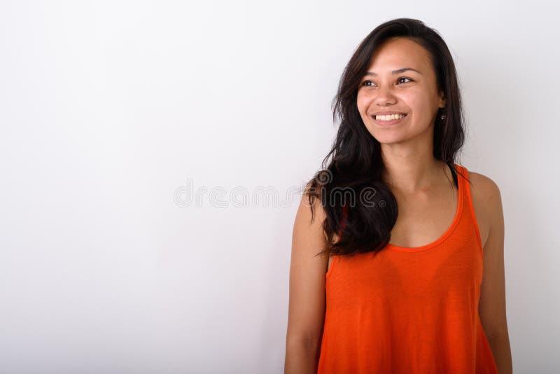 Студия снятая молодого счастливого азиатского whil женщины усмехаясь и думая стоковая фотография