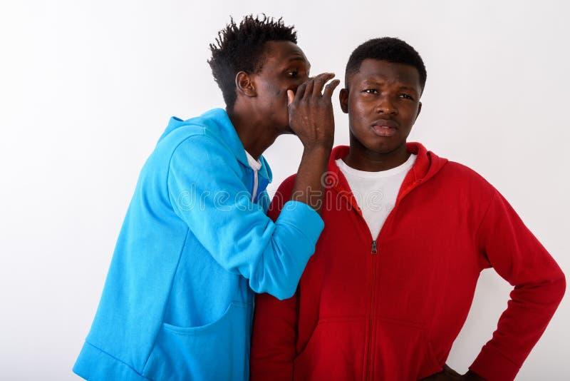 Студия снятая молодого тонкого человека черного африканца шепча к молодой стоковая фотография rf
