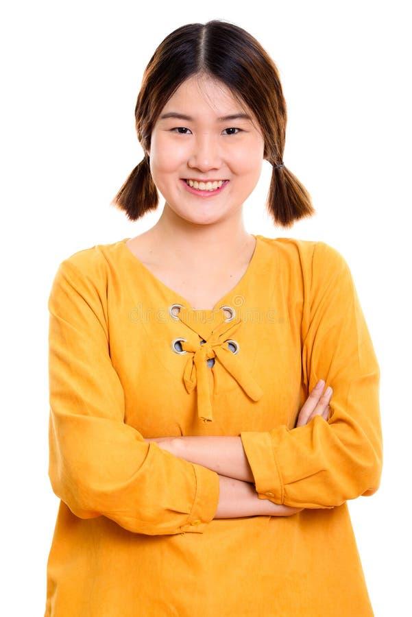 Студия снятая молодой счастливой азиатской женщины усмехаясь с пересеченными оружиями стоковое изображение