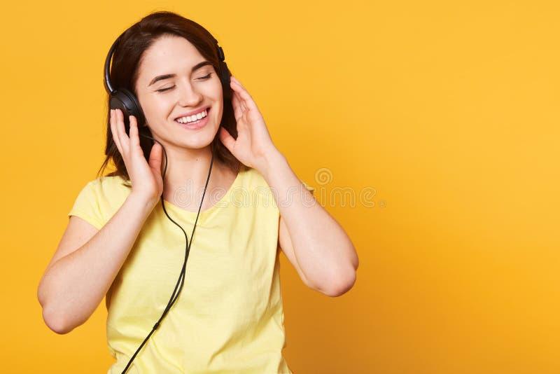 Студия снятая прелестной женщины с темными волосами наслаждается слушать музыку в наушниках, держит руки на наушниках, стоит с стоковые изображения rf