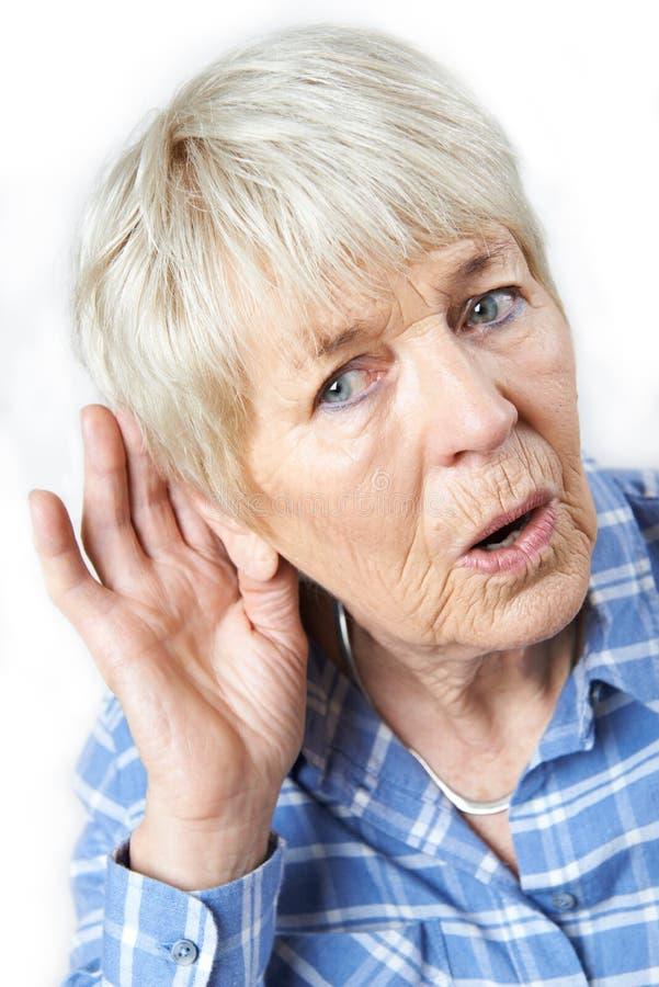 Студия снятая старшей женщины страдая от глухоты стоковые фото