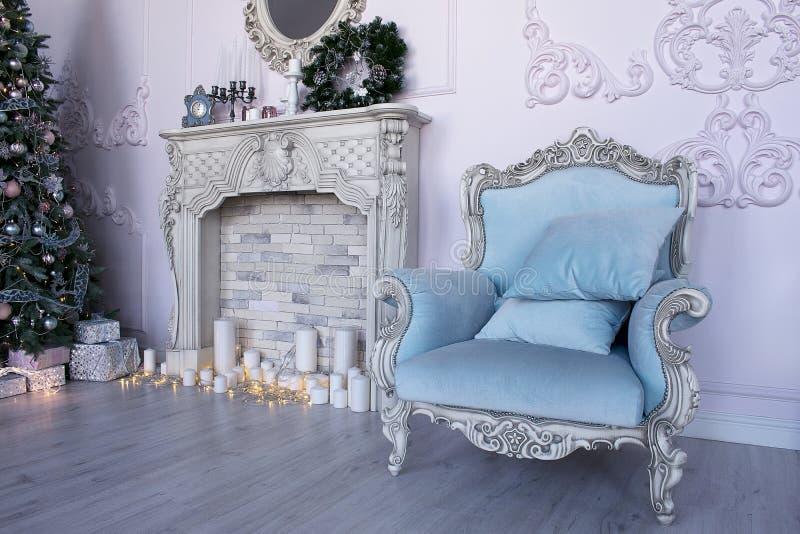 Студия с голубым креслом, камином и рождественской елкой стоковые изображения rf