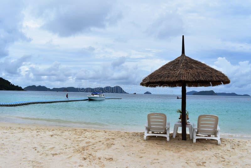 Стулья и зонтик в тропическом пляже на каникулах стоковая фотография rf