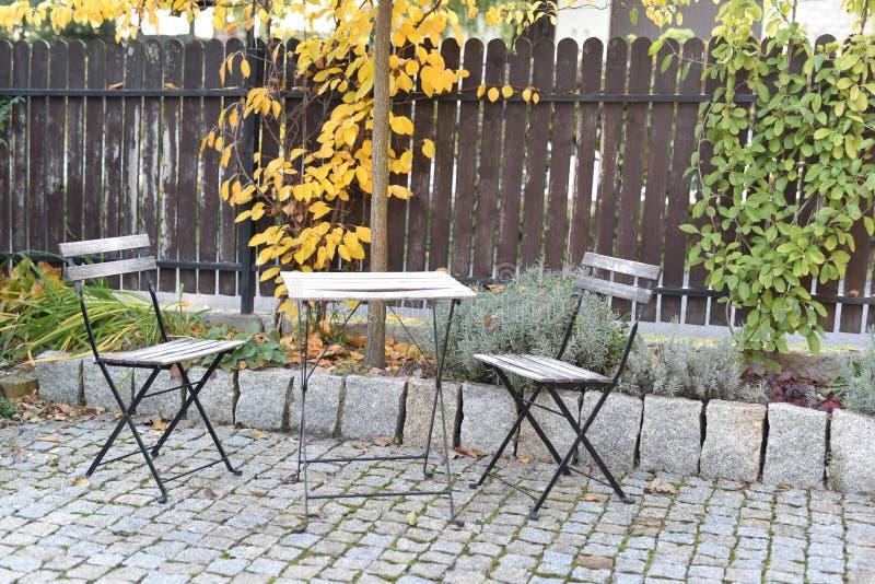 Стулья и таблица в саде осени стоковое фото