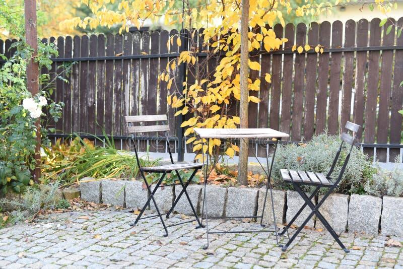 Стулья и таблица в саде осени стоковая фотография rf