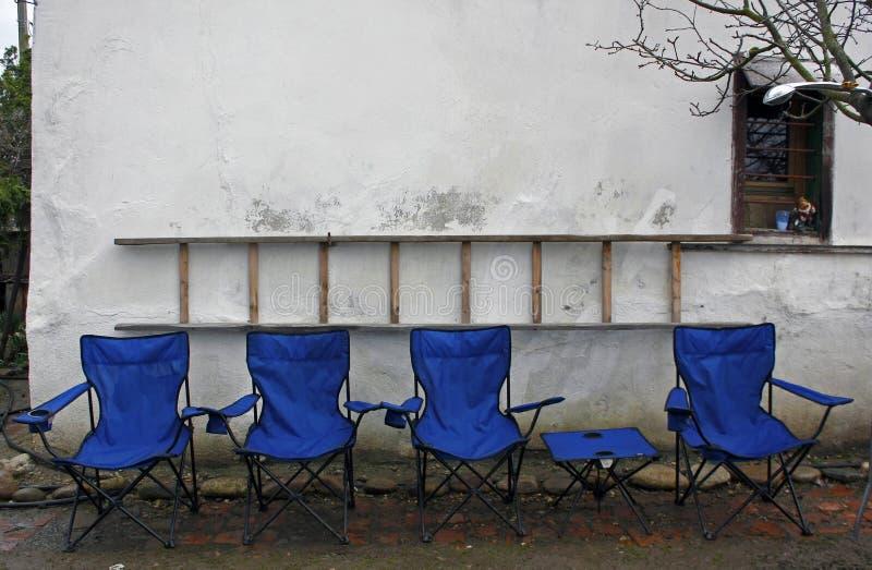 Стулья и таблица пустой голубой складчатости располагаясь лагерем выровнялись вверх перед деревенской белой стеной с лестницей на стоковая фотография