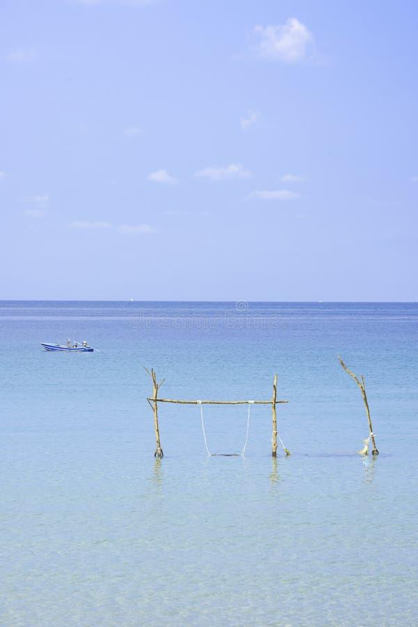 Стулья качания сделали из древесины и рыбацких лодок в небе и облаке предпосылки моря на Koh Kood, Trat в Таиланде стоковое изображение