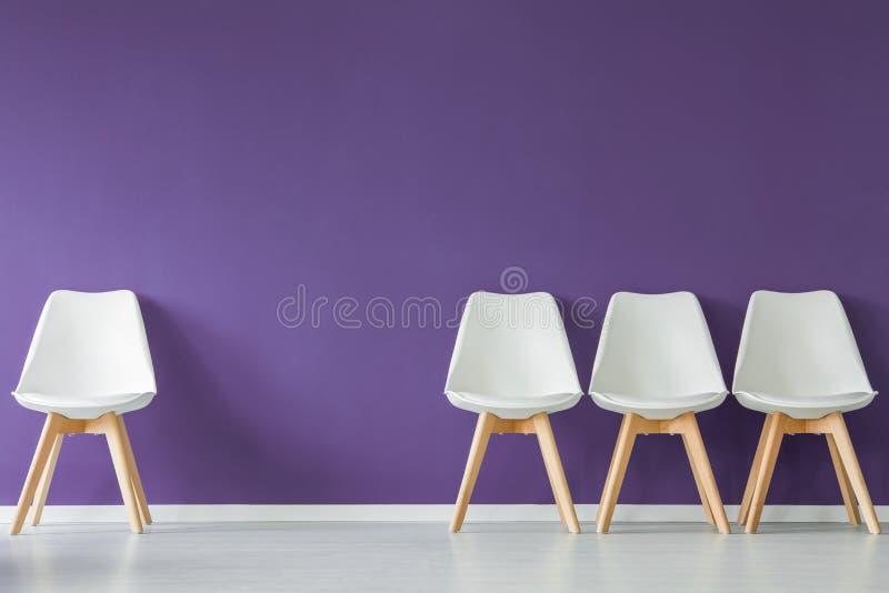 Стулья на фиолетовой стене стоковая фотография