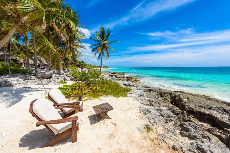 Стулья под пальмами на пляже рая на тропическом курорте Майя Ривьера - карибское побережье на Tulum в Quintana Roo, Мексике стоковое изображение