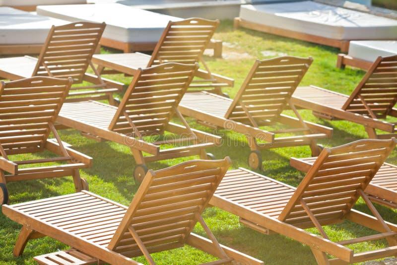 Стулья Poolside гостиницы на зеленом луге стоковое фото